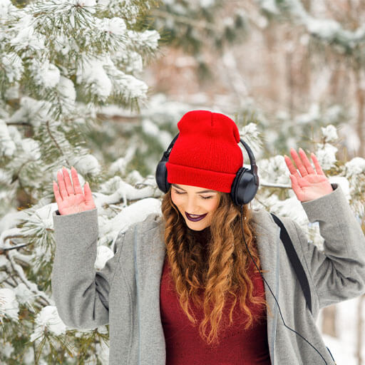 a girl dancing in the snow winter listening to music from headphones