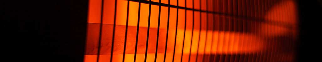 Detail of a close-up view of an infrared heater that glows red-orange behind its bars.