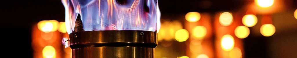 Detail of a close-up of the gas flames of a gas radiant heater in the dark and in the background further lights shine.