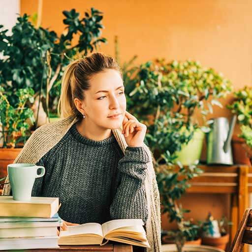 A young woman in a grey sweater sits wrapped in a blanket on a balcony at a table in front of books and a coffee cup.
