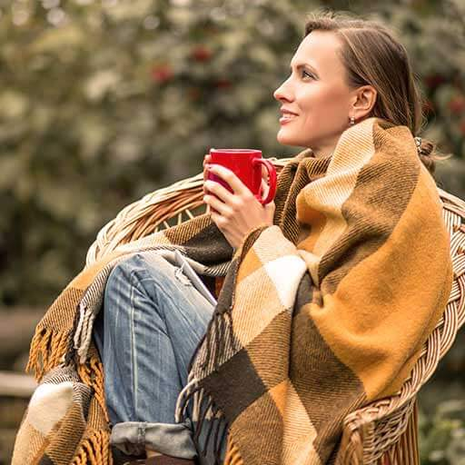 Young woman wrapped in jeans and yellow blanket is holding a red coffee cup and is sitting on a rattan chair in the garden.