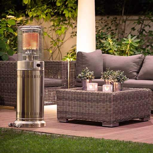 The chrome-plated blumfeldt Heatwave 2VA patio radiant heater stands on a terrace next to a grey rattan seating area.