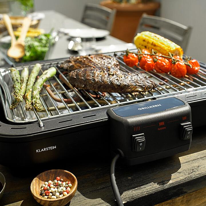 Grillkern als Elektrogrill auf dem Tisch mit Steaks und Gemüse
