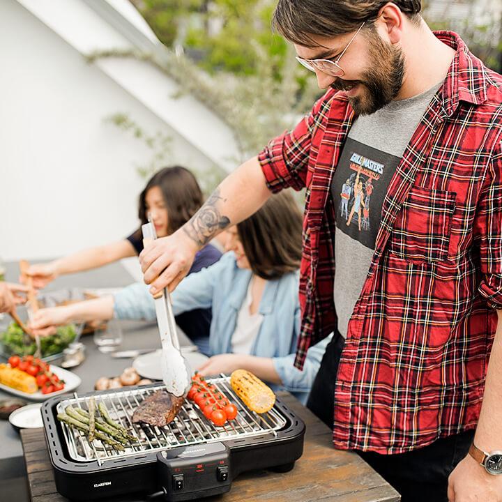 Gruppe grillt mit Grillkern Elektrogrill auf der Terrasse