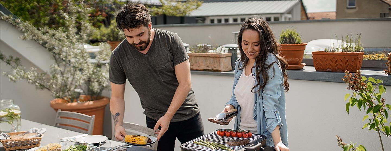 Paar grillt mit Grilkern als Tischgrill auf Terrasse